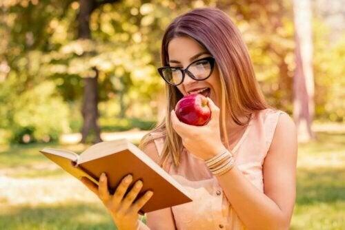 Een vrouw leest een boek terwijl ze een appel eet