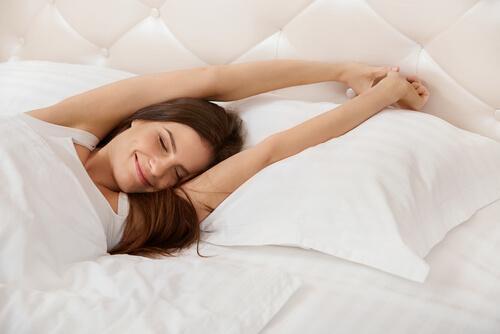 Een vrouw rekt zich uit in bed
