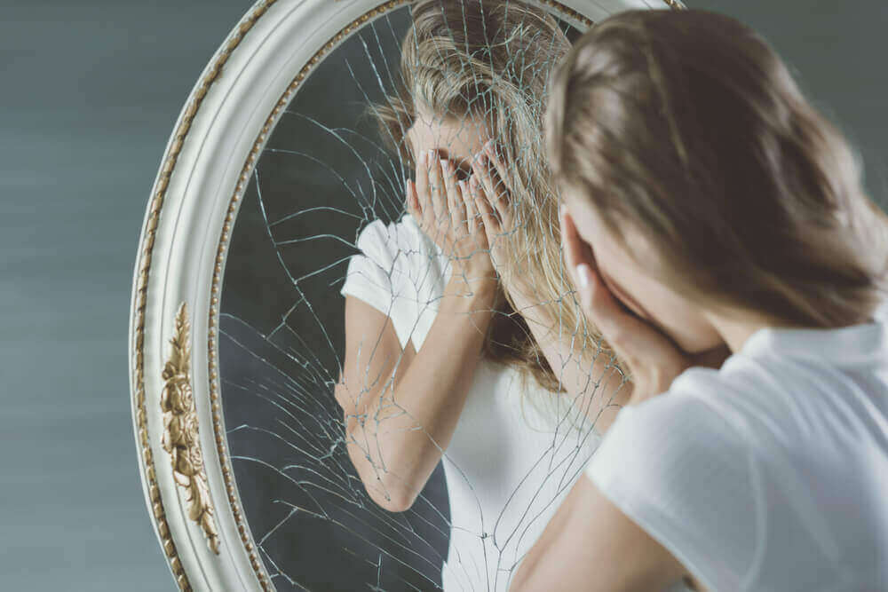 Vrouw bij een kapotte spiegel