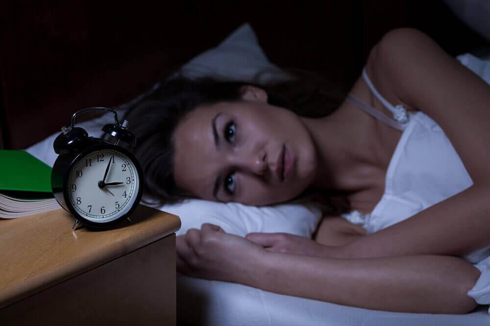 Vrouw ligt naar haar wekker te staren