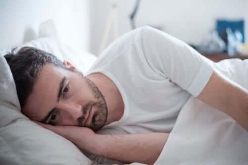 Een man ligt op bed en is depressief
