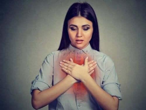 Een vrouw houdt de handen voor de borst