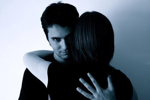 Een man kijkt spottend naar de camera terwijl hij een vrouw omhelst