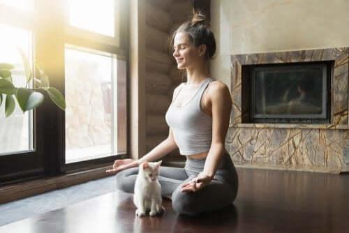 Een vrouw zit in een yogahouding met een kat