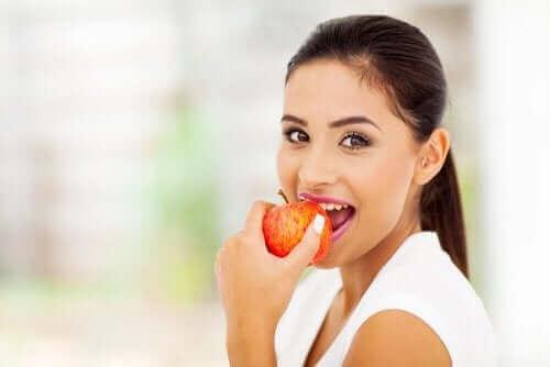 Vrouw eet een rode appel