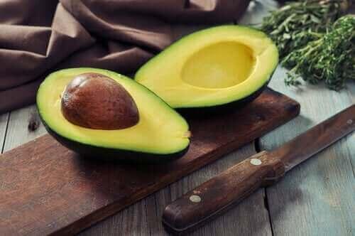 Een doorgesneden avocado op een plankje