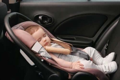 Een baby slaapt in een autozitje