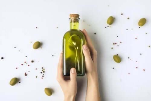 Olijfolie in een fles met olijven eromheen