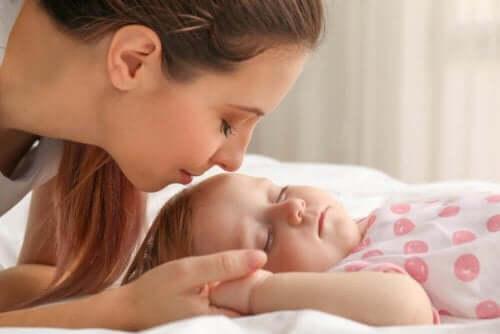 Een moeder kust het hoofdje van een baby