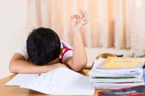 Een vermoeid kind leunt op zijn huiswerk