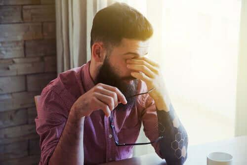 Een man wrijft in zijn ogen van vermoeidheid
