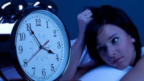 Een vrouw kijkt wanhopig naar de wekker