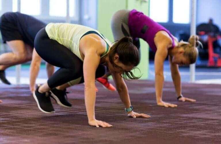 Groep vrouwen die burpees doen om fit te blijven