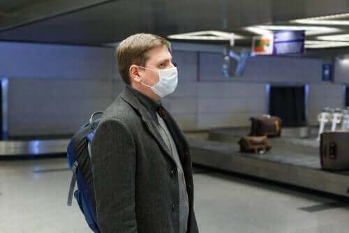 Man met een masker op een luchthaven