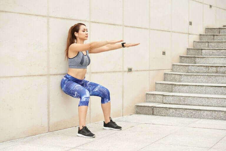 Vrouw doet een squat tegen de muur