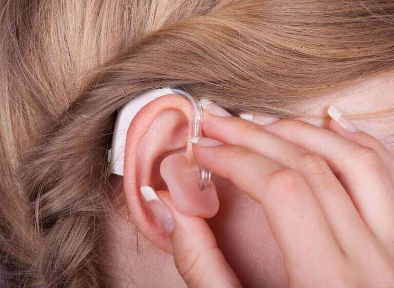 Vrouw doet gehoorapparaat in haar oor