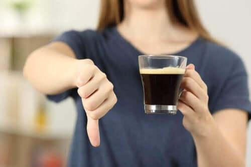 Een vrouw houdt een kop koffie in haar hand en doet haar duim omlaag
