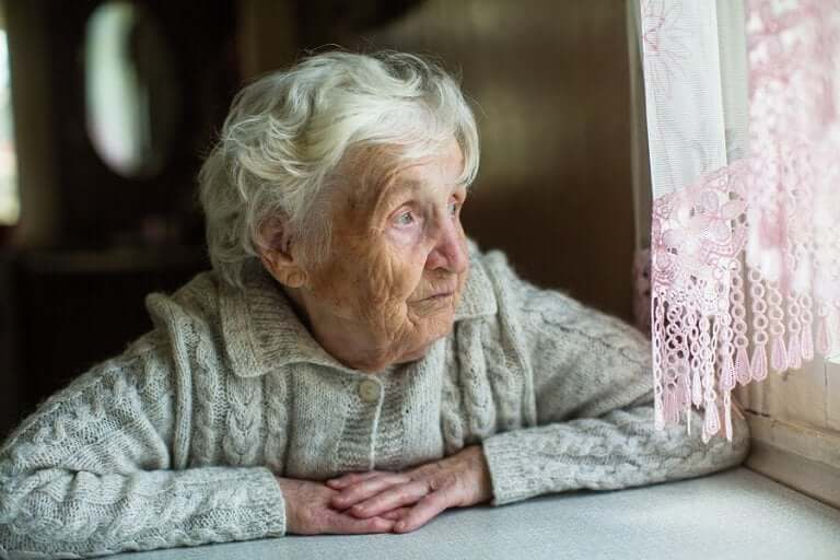 Bejaarde vrouw kijkt uit het raam