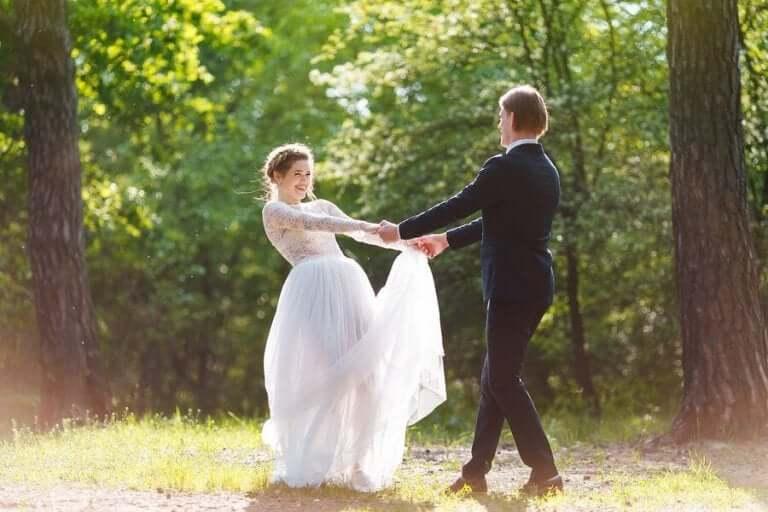 Bruid en bruidegom dansen in het bos