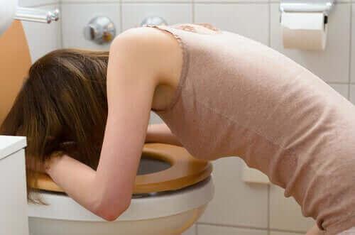 Vrouw is op het toilet aan het braken
