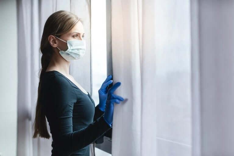 Vrouw met een masker bij een raam