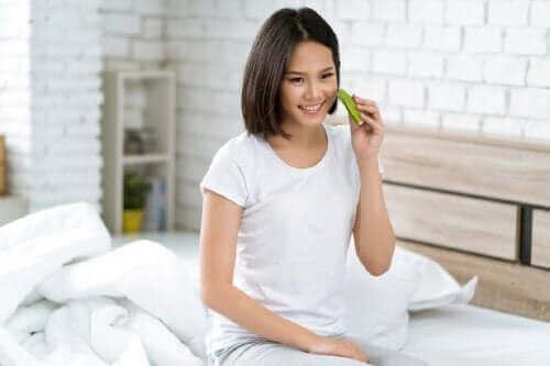 Een vrouw houdt aloëvera tegen haar gezicht