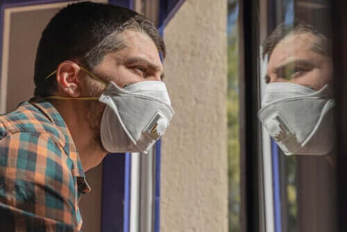 Man met angst voor het coronavirus kijkt uit het raam