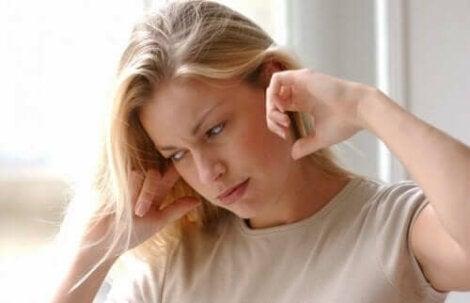 Een vrouw houdt haar vingers in haar oren