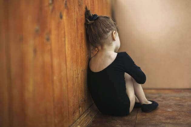 Meisje zit tegen de muur