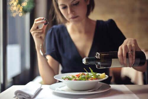 Vrouw giet olijolie op salade