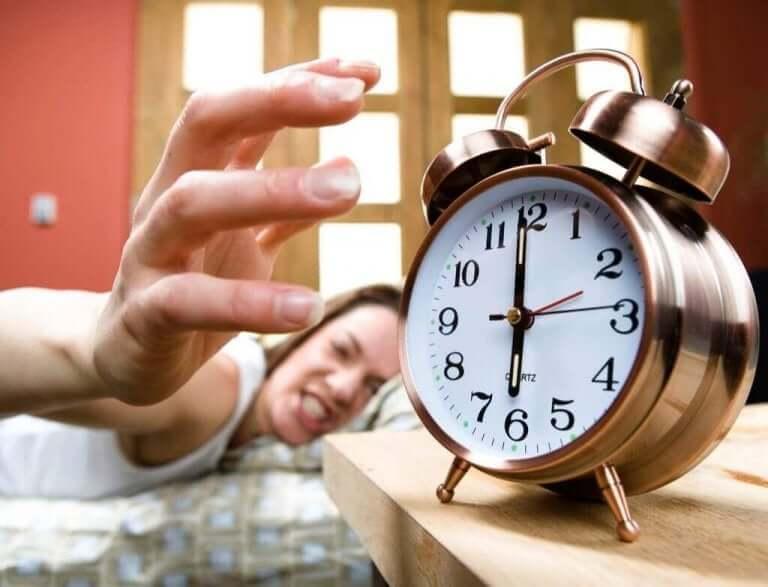 Vrouw die boos haar wekker uitzet