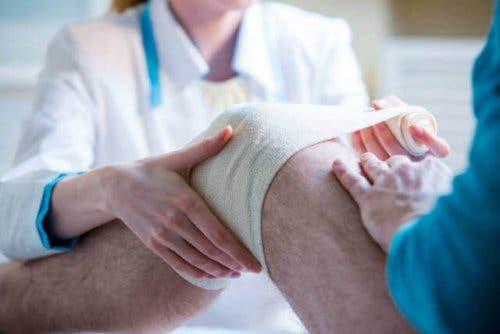 Een arts doet verband om een knie