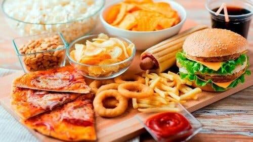 Een plank met fastfood en ongezonde snacks