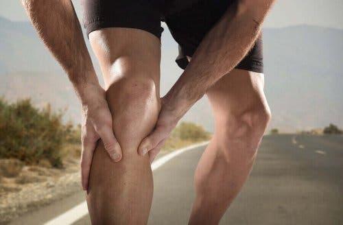 Een man grijpt naar zijn knie