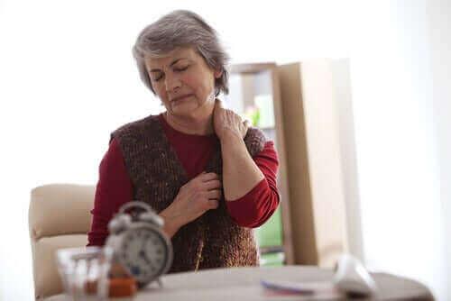 Een vrouw wrijft in haar nek