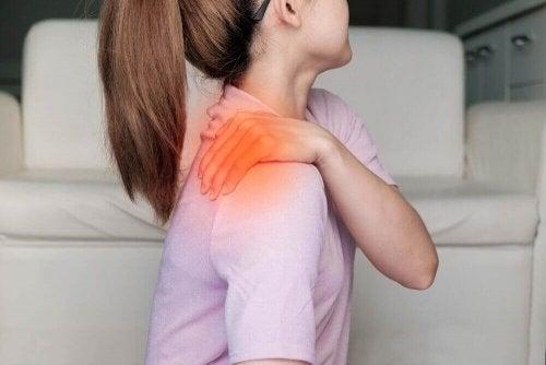 Een vrouw grijpt naar haar schouder