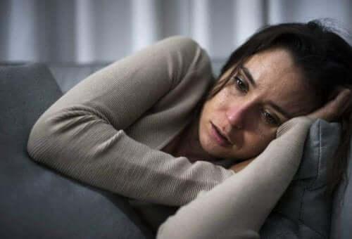 Een vrouw ligt verdrietig op de bank