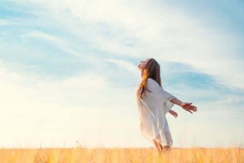 Een vrouw staat in een veld met haar armen naar achteren