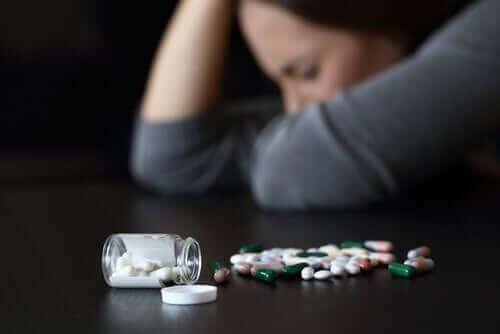 Vrouw zit naast potje pillen