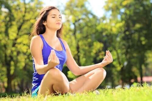 Vrouw zit op het gras te mediteren