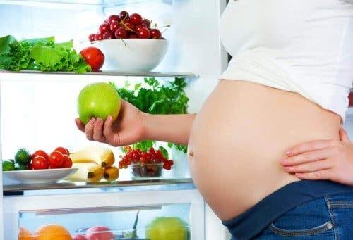 Zwangere vrouw staat bij allerlei groente en fruit