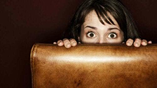 Een vrouw verstopt zich achter een stoel en kijkt erbovenuit