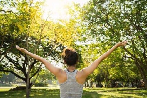 Een vrouw strekt haar armen uit tussen de bomen