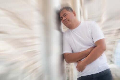Een man leunt tegen een muur met zijn armen om zijn buik