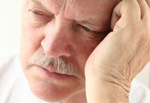 Een man houdt zijn hand tegen zijn gezicht
