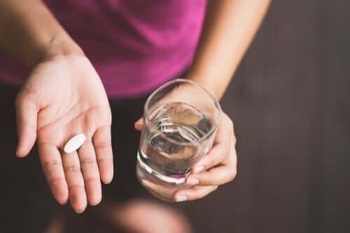 Een vrouw heeft een pil en een glas water in haar handen