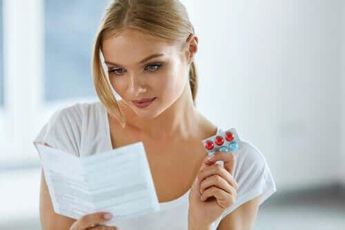Een vrouw leest de bijsluiter met pillen in haar hand