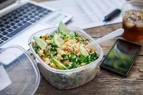 Een salade in een bakje op een bureau