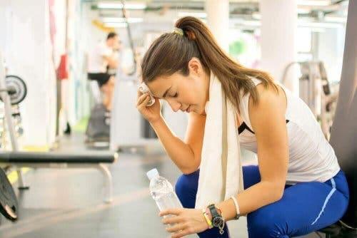 Een vrouw dept het zweet van haar voorhoofd in de sportschool