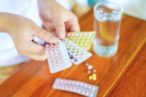 Drie strips anticonceptiepillen met een glas water ernaast